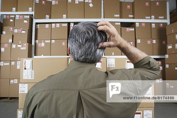 Businessman in warehouse scratching his head