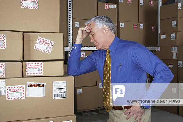 Businessman in warehouse with his head in his hand