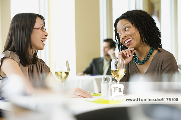 Two businesswomen laughing in restaurant