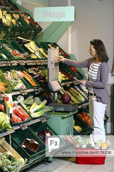 Frau wiegt Gemüse in der Gemüseabteilung ab  Selbstbedienung  Lebensmittelabteilung  Supermarkt  Deutschland  Europa