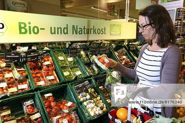 Frau kauft in der Obst- und Gemüseabteilung ein  Bioprodukte  Selbstbedienung  Lebensmittelabteilung  Supermarkt  Deutschland  Europa