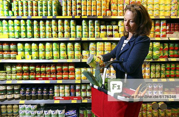 Frau kauft Gemüsekonserven ein  Selbstbedienung  Lebensmittelabteilung  Supermarkt  Deutschland  Europa
