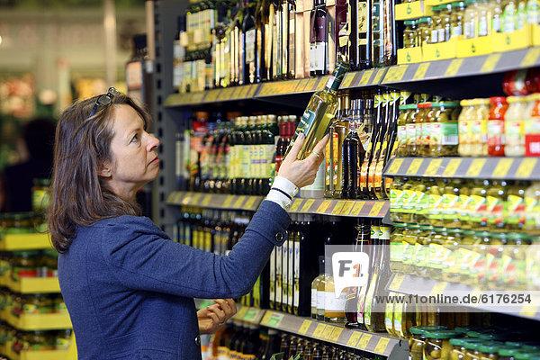 Frau kauft ein  vergleicht Essigsorten  Selbstbedienung  Lebensmittelabteilung  Supermarkt  Deutschland  Europa