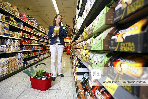 Frau kauft Mehl  Backzubehör ein  Selbstbedienung  Lebensmittelabteilung  Supermarkt  Deutschland  Europa