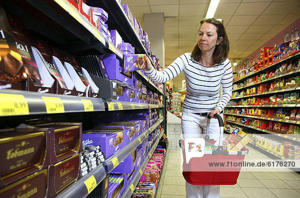 Frau am Schokoladenregal  Selbstbedienung  Lebensmittelabteilung  Supermarkt  Deutschland  Europa