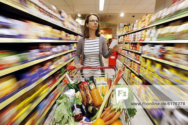 Frau schiebt einen vollen Einkaufswagen durch einen Gang einer Lebensmittelabteilung  Selbstbedienung  Supermarkt  Deutschland  Europa