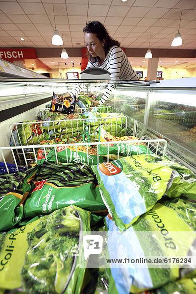Frau kauft tiefgefrorenes Gemüse ein  Tiefkühlabteilung  Lebensmittelabteilung  Selbstbedienung  Supermarkt  Deutschland  Europa