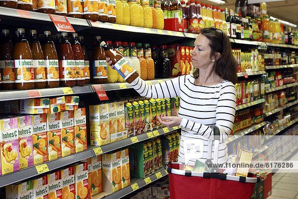 Frau schaut sich die Inhaltsstoffe einer Saftflasche an  Lebensmittelabteilung  Selbstbedienung  Supermarkt  Deutschland  Europa