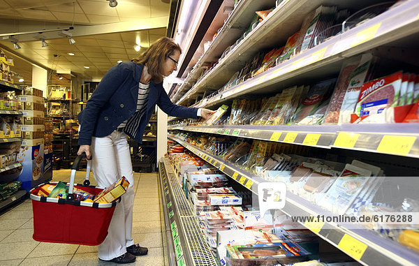 Frau schaut sich abgepackte Wurst- und Fleischprodukte in einem Kühlregal an  Lebensmittelabteilung  Selbstbedienung  Supermarkt  Deutschland  Europa