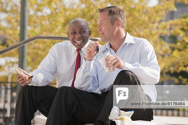 Businessmen eating lunch on steps