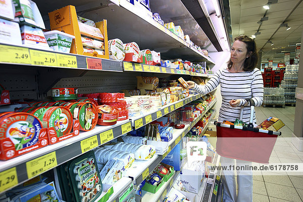 Cooler  woman shopping for a variety of dairy products  self-service  food department  supermarket  Germany  Europe