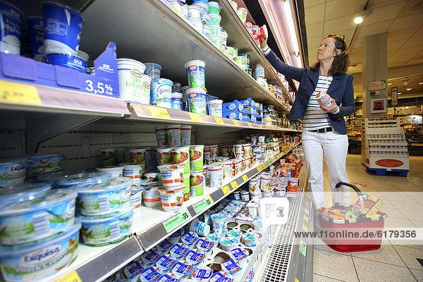 Kühlregal  Frau kauft verschiedene Milchprodukte ein  Selbstbedienung  Lebensmittelabteilung  Supermarkt  Deutschland  Europa