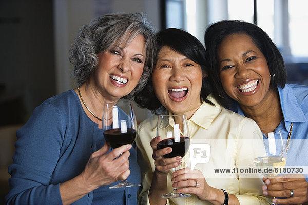 Multi-ethnic women drinking wine