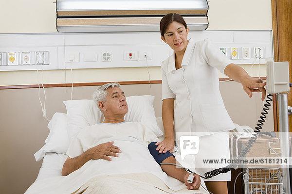 Nurse Taking Patient Blutdruck im Krankenhauszimmer
