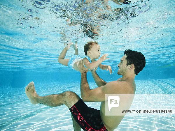 Menschlicher Vater  Unterwasseraufnahme  schwimmen  Tochter