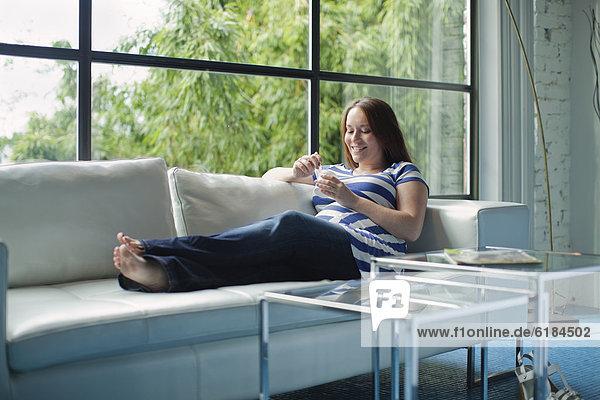 Pregnant Caucasian woman eating on sofa