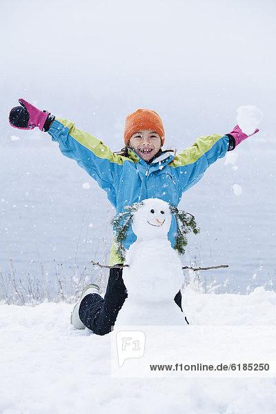 Mixed race girl building snowman