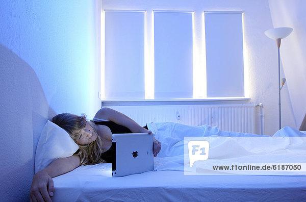 Junge Frau surft im Bett mit einem iPad  Tablet-Computer per Drahtlosverbindung im Internet