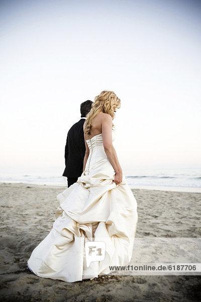 Braut und Bräutigam Wandern am Strand