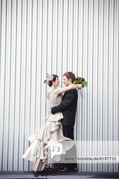 Braut mit Sektglas umarmt Bräutigam