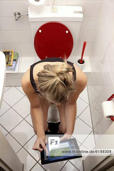 Junge Frau auf der Toilette mit einem iPad  Tablet-Computer  drahtloser Internet-Zugang