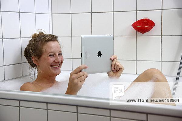 Junge Frau in der Badewanne mit einem iPad  Tablet-Computer  drahtloser Internet-Zugang
