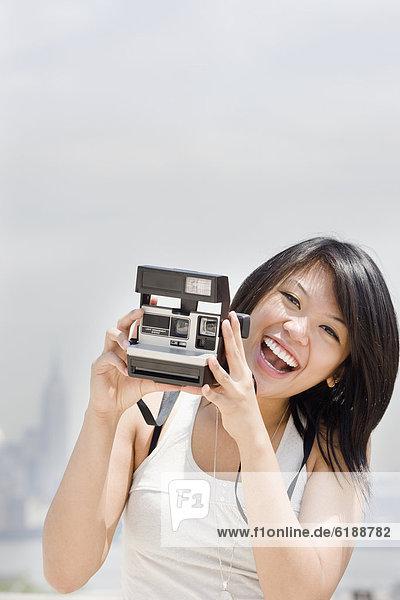 Asiatische Frau mit Sofortkamera
