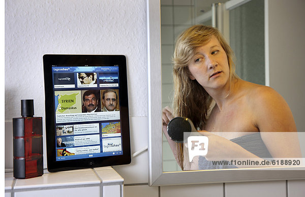 Junge Frau liest morgens im Badezimmer beim Haare föhnen eine Nachrichtenseite auf einem iPad  Tablet-Computer  per drahtlosem Internetzugang