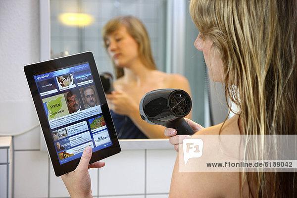 Junge Frau liest morgens beim Haare föhnen im Badezimmer eine Nachrichtenseite auf einem iPad  Tablet-Computer  per drahtlosem Internetzugang