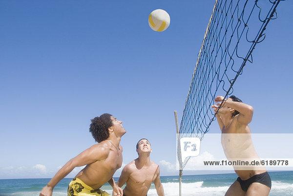 Drei Freunde spielen Beachvolleyball