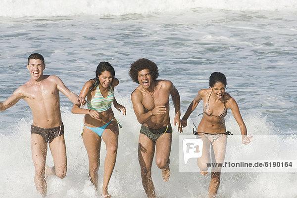 Freundschaft  Strand  rennen  multikulturell  Brandung