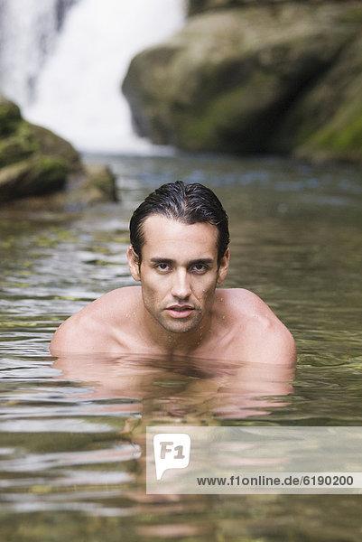 Hispanic man swimming in stream