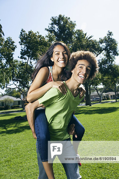Teenager carrying girlfriend on his back in park
