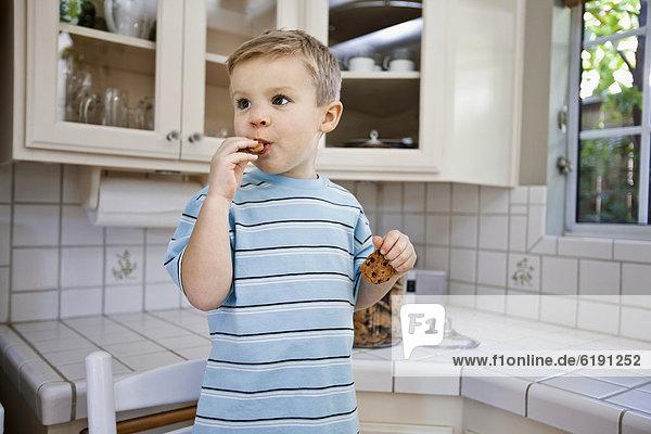 Europäer  Junge - Person  Küche  essen  essend  isst  Keks