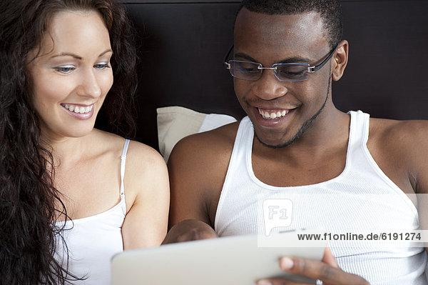 sitzend  Zusammenhalt  sehen  Bett  Tablet PC