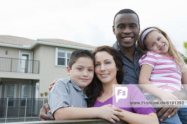 Glückliche Familie umarmt sich im Freien