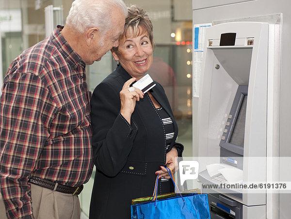 Älteres hispanisches Paar  das Geld von Geldautomaten abzieht