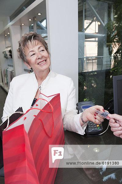 Senior Hispanic woman paying with credit card