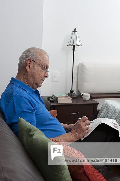 sitzend  Senior  Senioren  Mann  sehen  Couch  Hispanier  Zeitung