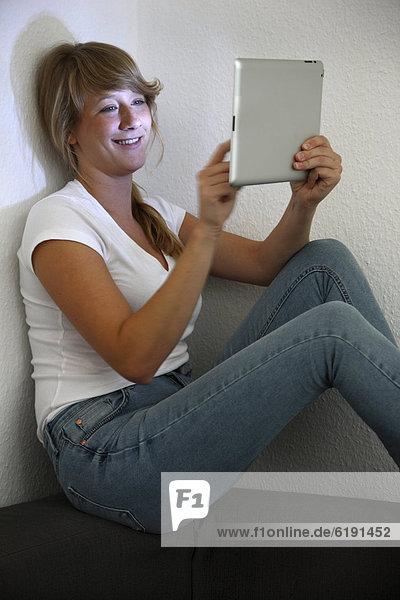 Junge Frau sitzt auf Sofa und surft drahtlos im Internet mit einem iPad Tablet-Computer