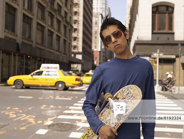 Indian man on city street holding skateboard