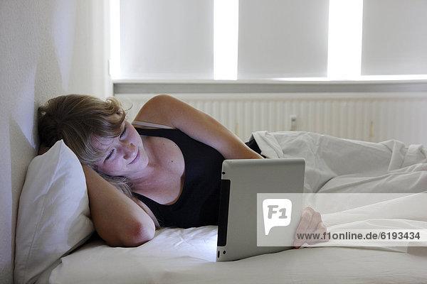 Junge Frau im Bett surft mit einem iPad  Tablet-Computer per Drahtlosverbindung im Internet
