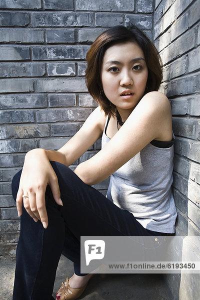 angelehnt  Frau  ernst  Wand  Ziegelstein  chinesisch
