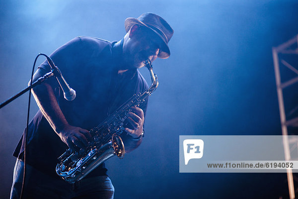 Black musician playing saxophone on stage