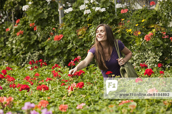 Caucasian woman shopping for flowers in plant nursery