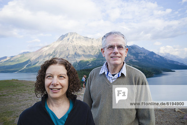 Caucasian couple standing outdoors with mountain in background