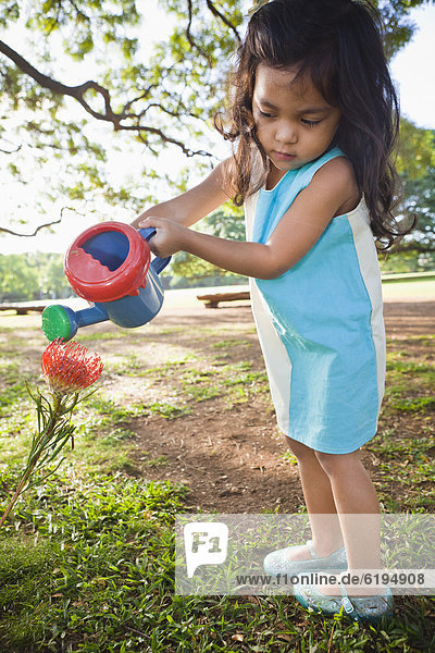 Girl watering flower with watering can