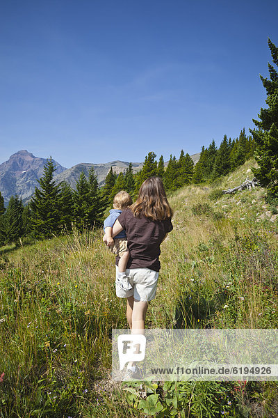 Mother carrying son on remote mountain path