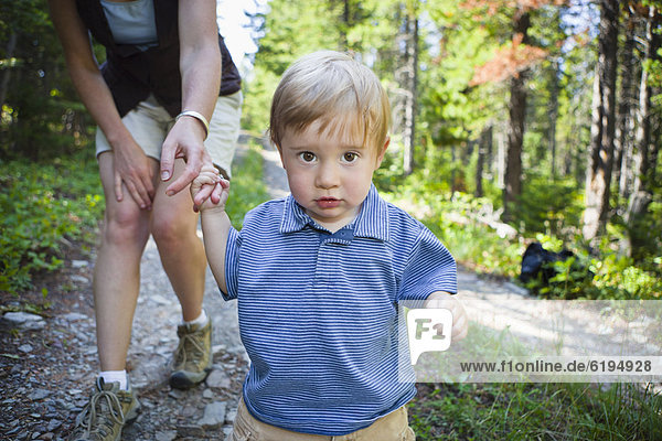 Mother and son walking on remote forest path
