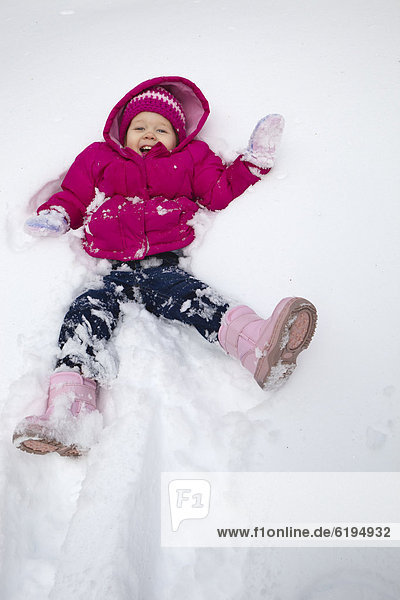 Grinning girl laying in snow